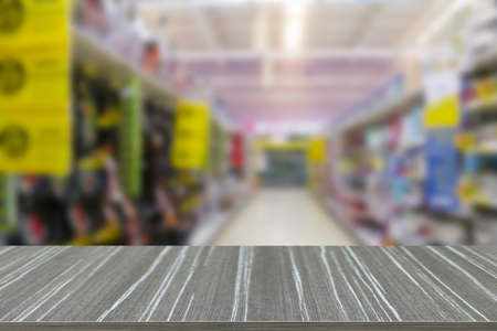 empty wooden table with goods on the shelf in supermarket shopping mart blur background for displaying your product