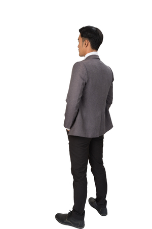 Full length of thoughtful businessman standing back to camera on white backgroundの写真素材