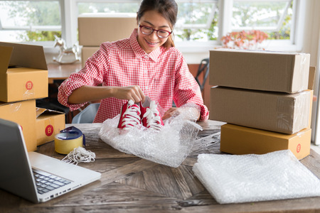 Photo pour young start up small business owner packing shoes in the box at workplace. freelance woman entrepreneur SME seller prepare product for packaging process at home.  Online selling, internet marketing, e-commerce concept - image libre de droit