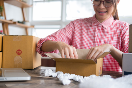 Photo pour young start up small business owner packing cardboard box at workplace. freelance woman entrepreneur SME seller prepare parcel box of product for deliver to customer.  Online selling, internet marketing, e-commerce, shipping concept - image libre de droit