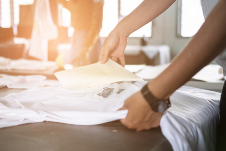 Foto de Young woman pull out paper from waterproof film on fabric. worker working on manual screen printing on t-shirt at her shop. - Imagen libre de derechos