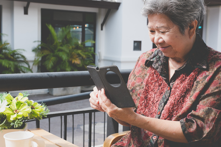 Photo pour asian elder woman holding mobile phone in cafe. elderly female texting message, using app with cellphone. senior use smartphone to connect social network - image libre de droit