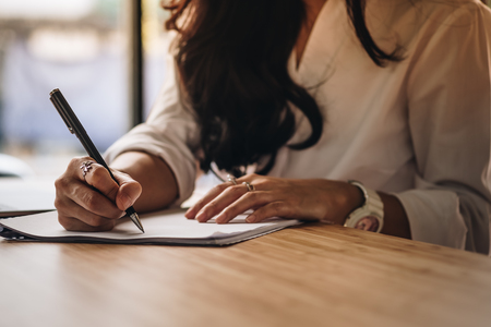 asian businesswoman writing on paper at workplace. young female entrepreneur woman handwriting note at office. paperwork on table.