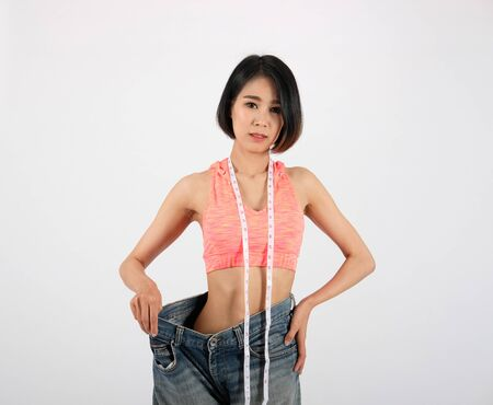 Photo pour sporty fitness woman in loose jeans after losing weight on white background. healthy sport lifestyle - image libre de droit