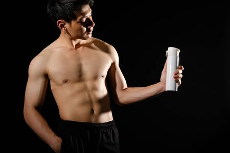 Photo pour portrait of athletic muscular bodybuilder man with naked torso six pack abs holding protein drink. fitness workout concept - image libre de droit