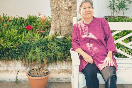 old elder woman resting in garden. asian elderly female relaxing in park. senior leisure lifestyle