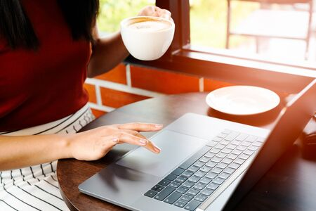 Photo for Asia woman hold cup of coffee while typing on laptop keyboard. Woman working at office with coffee - Royalty Free Image
