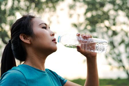 Photo for Fitness Asia Woman Drinking Water after Running - Royalty Free Image