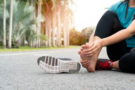 Asia woman massaging her painful foot while exercising. Running Sport and excercise injury concept