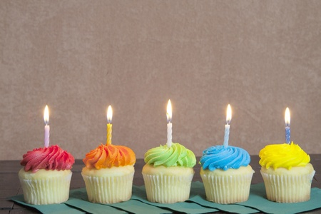 Photo for Five cupcakes with lit candles sitting in a row on green napkins for a party. - Royalty Free Image