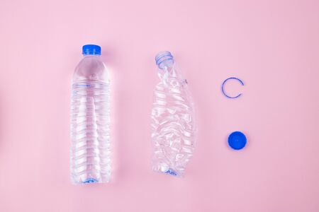 Foto de Full drinking water contained in transparent plastic bottle and empty crushed bottle preparing for recycling, plastic label removed, blue cap isolated. Flat lay set on pink colour background. - Imagen libre de derechos