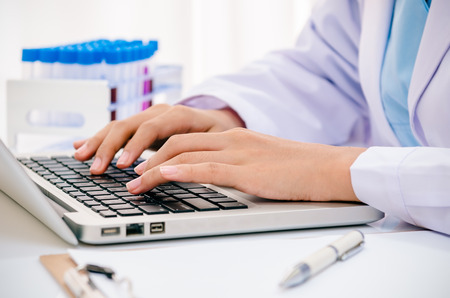 close up of scientist recording chemical tubs onto computer