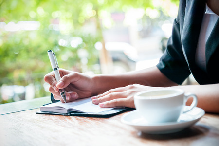 Photo pour close up of woman writing journal and cup of coffee - image libre de droit