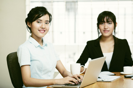Beautiful young businesswomen working and typing