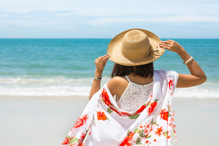 Foto de Back view of Travel asia woman with hat and dress looking out of sea on a beach in summer, Koh Samet, Thailand - Imagen libre de derechos