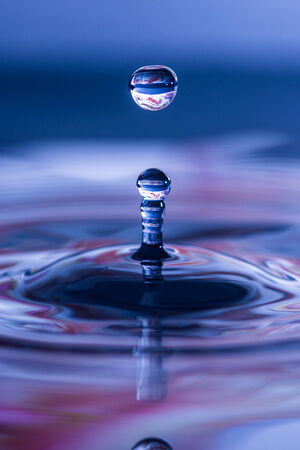 Splash rising from the water s surface after impact of water droplet