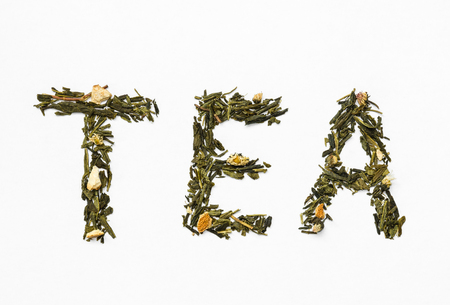 green tea with orange peel and chamomile on white background