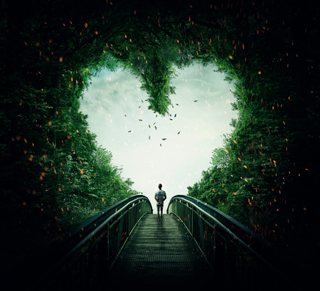 Photo pour Boy walking on a bridge through the heart shape woods, following the light. Follow your heart concept - image libre de droit