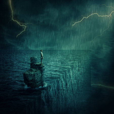 Lost man abandoned on a rock cliff island, in the middle of the ocean, in a stormy night. Adventure and journey concept at the edge of the world. Parallel universe, multiverse theory.