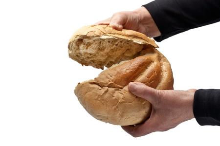 An elderly woman breaking a loaf of bread