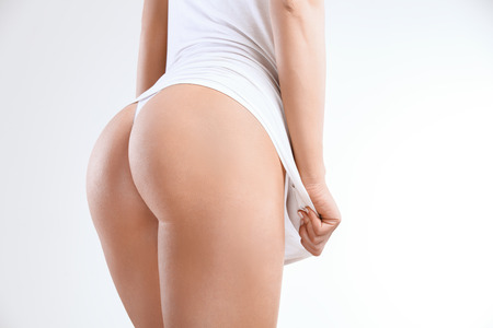 Photo pour Closeup of a Beautiful Woman Showing Perfect Buttocks on White - image libre de droit
