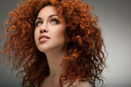 Red Hair. Beautiful Woman with Curly Long Hair.