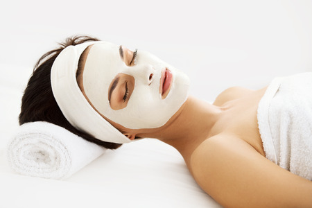 Foto de Cosmetic Mask. Beautiful Young Woman Getting a Beauty Treatment in Spa Salon. Isolated on White Backround - Imagen libre de derechos
