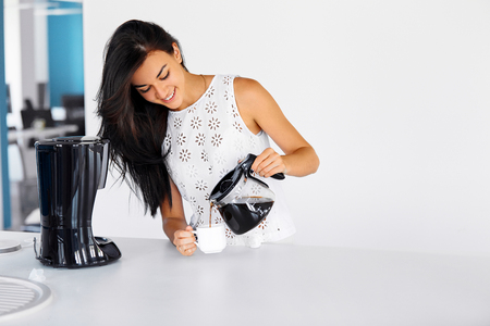 Photo pour Photo of a woman on her break pouring herself a mug of hot filtered coffee from a glass pot - image libre de droit