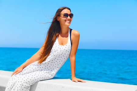 Young beautiful woman with long hair enjoying summer. Blue Mediterranean Sea View on background.