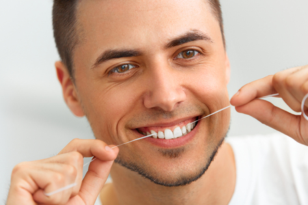 Photo pour Closeup of young man flossing his teeth. Cleaning teeth with dental floss - image libre de droit