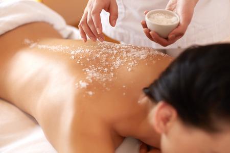 Photo pour Spa Woman. Brunette Getting a Salt Scrub Beauty Treatment in the Health Spa. Body Scrub. - image libre de droit