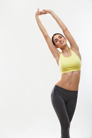 Foto de Woman doing stretching exercises against white - Imagen libre de derechos