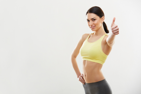Photo for Happy fitness Young Woman Showing Thumbs Up. - Royalty Free Image