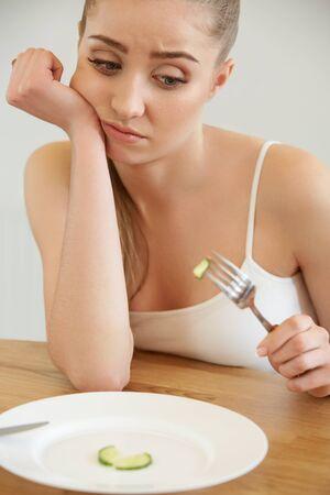 Beautiful Young Woman eats vegetable