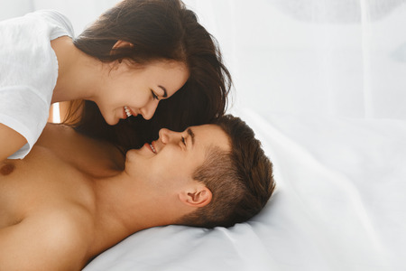 Photo pour Happy smiling couple in love hugging and kissing each other while lying in bed, romantic scene in bedroom - image libre de droit