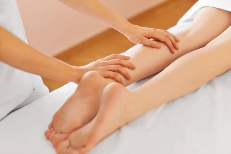 Young Woman Receiving Leg Massage at Spa Center. Body Care