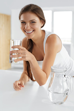 Photo for Beauty, Diet Concept. Happy Smiling Woman Drinking Fresh Crystal Clear Water From A Glass. Healthcare. Healthy Lifestyle And Eating. Health, Dieting, Fitness Concept. Drinks - Royalty Free Image
