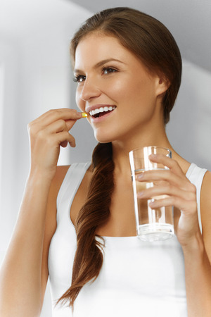 Photo pour Vitamins. Healthy Diet, Eating, Lifestyle. Happy Smiling Woman Taking Pill With Cod Liver Oil Omega-3 And Holding A Glass Of Fresh Water. Healthcare And Beauty. Vitamin D, E, A Fish Oil Capsules. Nutrition. - image libre de droit