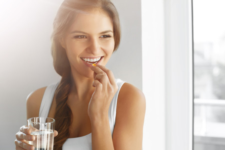 Foto de Diet. Nutrition. Vitamins. Healthy Eating, Lifestyle. Close Up Of Happy Smiling Woman Taking Pill With Cod Liver Oil Omega-3 And Holding A Glass Of Fresh Water In Morning. Vitamin D, E, A Fish Oil Capsules. - Imagen libre de derechos
