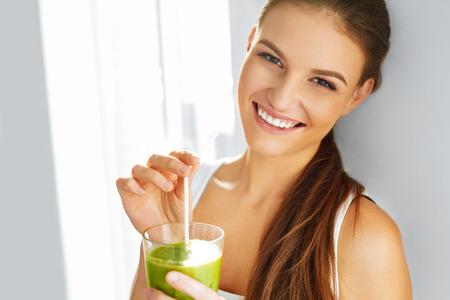 Foto de Healthy Food Eating. Happy Beautiful Smiling Woman Drinking Green Detox Vegetable Smoothie. Diet. Healthy Lifestyle, Vegetarian Meal. Drink Juice. Health Care And Beauty Concept. - Imagen libre de derechos