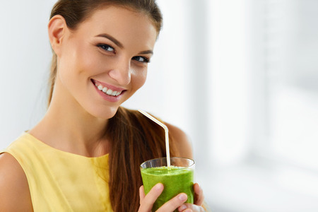 Healthy Food And Eating. Happy Young Woman Drinking Green Detox Vegetable Smoothie. Healthy Lifestyle, Vegetarian Diet And Meal. Drink Juice. Health Care And Beauty Concept.の写真素材