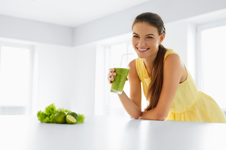Foto de Healthy Meal. Happy Beautiful Smiling Woman Drinking Green Detox Vegetable Smoothie. Healthy Lifestyle, Food And Eating. Drink Juice. Diet, Health And Beauty Concept. - Imagen libre de derechos