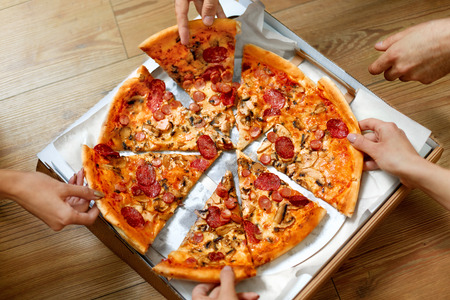 Photo pour Eating Food. Close-up Of People Hands Taking Slices Of Pepperoni Pizza. Group Of Friends Sharing Pizza Together. Fast Food, Friendship, Leisure, Lifestyle. - image libre de droit