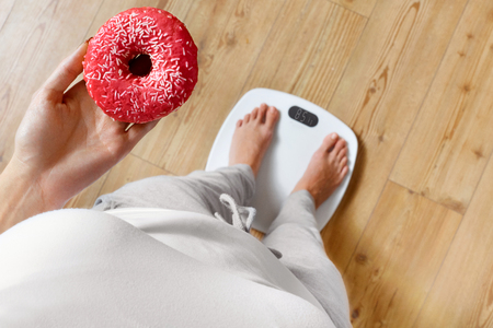 Foto de Diet. Woman Measuring Body Weight On Weighing Scale Holding Donut. Sweets Are Unhealthy Junk Food. Dieting, Healthy Eating, Lifestyle. Weight Loss. Obesity. Top View - Imagen libre de derechos