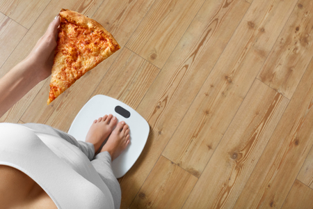 Diet And Fast Food Concept. Overweight Woman Standing On Weighing Scale Holding Pizza. Unhealthy Junk Food. Dieting, Lifestyle. Weight Loss. Obesity. Top View