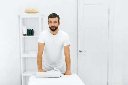Body Care. Portrait Of Masseur Standing By Massage Table In Spa Salon. Physical Therapist In Medical Office. Beauty Treatment, Massage Therapy. Healthcare, Medicine Concept. Wellness, Lifestyle.