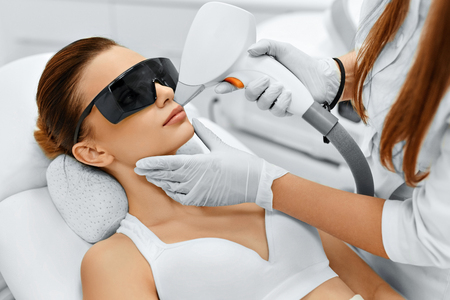 Photo pour Face Care. Facial Laser Hair Removal. Beautician Giving Laser Epilation Treatment To Young Woman's Face At Beauty Clinic. Body Care. Hairless Smooth And Soft Skin. Health And Beauty Concept. - image libre de droit