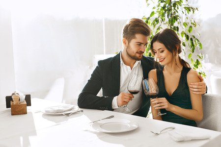 Foto de Couple In Love. Happy Romantic Smiling Elegant People Having Dinner, Drinking Wine, Celebrating Holiday, Anniversary Or Valentine's Day In Gourmet Restaurant. Romance, Relationships Concept. - Imagen libre de derechos