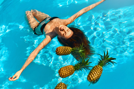 Healthy Diet, Nutrition. Health Care Concept. Smiling Young Woman Relaxing With Fresh Organic Pineapples In Refreshing Pure Water In Swimming Pool. Fruits For Beauty. Lifestyle. Summer Travel Vacation