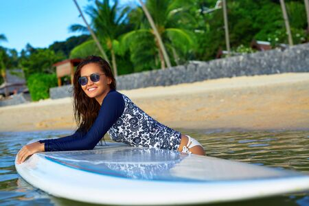 Photo pour Sports. Active Lifestyle. Healthy Beautiful Happy Fit Young Asian Woman In Blue Wetsuit On Surfing, Surf Board In Sea Water. Summer Holidays Travel Vacation. Exotic Resort. Leisure Activity, Wellness - image libre de droit